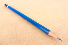 Long blue pencil on wood background Royalty Free Stock Photography
