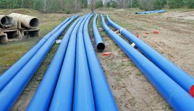 Long Blue Plastic Sewer Pipes In The Wood Industrial Landscape Royalty Free Stock Photo