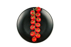 Long branch of organic ripe fresh cherry tomatoes on a black plate isolated on a white background. Top view. Stock Photography