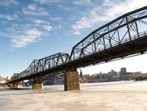 Long bridge!. Long metal bridge over frozen river royalty free stock images
