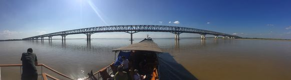 Long bridge crossing a Burmese river. View from a traditional boat, navigating the waters. Myanmar royalty free stock photos