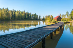 Long bridge going to the house on a small island. Long bridge going to the house on a small island, located on forest lake Royalty Free Stock Images
