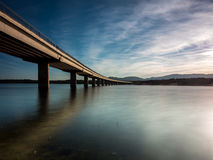 Long bridge over a lake with still water at evening Royalty Free Stock Photos