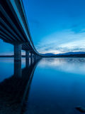 Long bridge over a lake with still water at evening Royalty Free Stock Photography