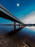 Long bridge over a lake with under full moon at evening Royalty Free Stock Images