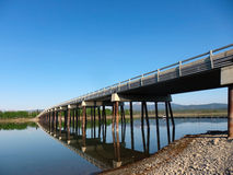 A long bridge spanning the carcross river Stock Image