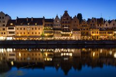 Long Bridge waterfront in Gdansk at dusk. Scenic view of lit old buildings along the Long Bridge waterfront and their reflections on the Motlawa river at the Royalty Free Stock Photography