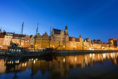 Long Bridge waterfront in Gdansk at dusk. Scenic view of a tourist sailing boat and lit old buildings along the Long Bridge waterfront at the Main Town in Gdansk Stock Image
