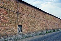 Long brown brick wall along an asphalt road. Part of the brown brick wall of the building near the road on the street Royalty Free Stock Image