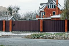 A long brown metal fence and a closed door on the street by the road. Private long brown metal fence and closed door on a winter street by the road royalty free stock photo