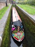 Long canal narrowboat inside lock. A long passenger carrying narrowboat inside a lock on the Staffordshire and Worcestershire Canal in England royalty free stock photos