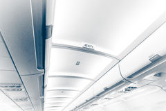 Long ceiling in airplane with exit sign Stock Photos