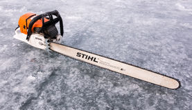 A long chained chainsaw for ice sawing lays on ice of a lake in Savonlinna, Finland Stock Image