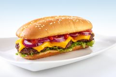 Long cheeseburger. On plate , with three grilled patties , lettuce ,  red onion , cheddar cheese and ketchup Stock Image
