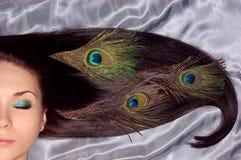 Long cheveu de beau brunet décoré du paon image stock