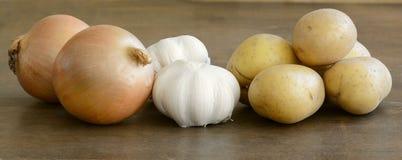 Long close up of potatoes, onions, and garlics Royalty Free Stock Photos