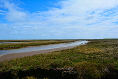 Long coastal stream / river and blue sky, Blakeney Point, Norfolk,  United Kingdom. The Norfolk Coast Area of Outstanding Natural Beauty is a protected landscape Royalty Free Stock Images