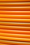 Long coils of orange plastic pipes for the installation of  opti Royalty Free Stock Image