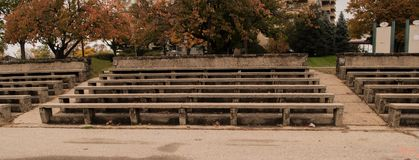 Stone and concrete bleachers in a park. Long concrete benches with stone bases set up like bleachers with trees in background royalty free stock images
