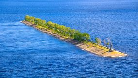 A long concrete breakwater with green trees and a lighthouse in the middle of a blue river with waves royalty free stock images