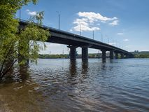 Long concrete bridge across the wide river. With blue sky. Bottom view Royalty Free Stock Image
