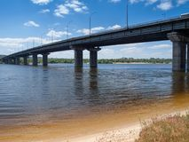 Long concrete bridge across the wide river. With sandy shore. Bottom view Royalty Free Stock Photo