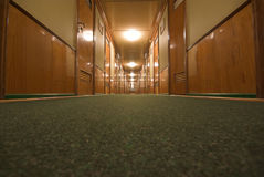 Long corridor. Wide-angle shot of long corridor with doors from floor level. Cruise ship interior Royalty Free Stock Photo