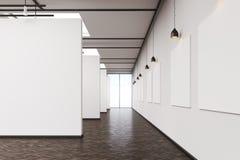Long corridor in art gallery with dark wood floor. Long corridor in an art gallery. White walls with posters and dark wood floor. Concept of modern art Royalty Free Stock Photo
