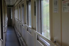 The long corridor of the compartment train, the transparent windows stock photo