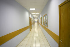 Long corridor. Long empty corridor with a floor covered with tiles Royalty Free Stock Photo