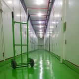 Long corridor, green floor and cart, self-storage facilities interior. Units with locks on both sides Royalty Free Stock Photography
