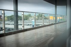 Long corridor with hardwood floor and car park background stock image