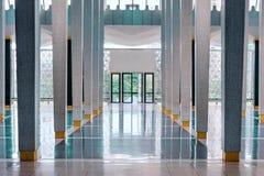 Long corridor between many columns with open doors in the end, s stock image