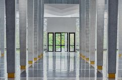 Long corridor between many columns, open doors in the end, symmetric modern hall. In National Mosque Masjid Negara, Kuala Lumpur, Malaysia. Functional interior royalty free stock photos