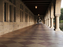 Long corridor at Stanford. California. Amber sculpted stones columns, large mosaic pavement Stock Photography