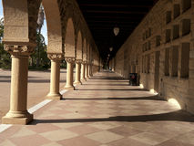 Long corridor at Stanford. California. Amber sculpted stones columns, large mosaic pavement Stock Images