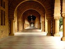 Long corridor at Stanford. California. Amber sculpted stones columns, large mosaic pavement Stock Photos