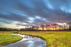 Long coucher du soleil d'Exposue au-dessus de paysage de rivière Image libre de droits