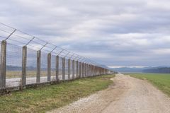 Long country road stretching off past a lone tree to the distant horizon with fence on the right royalty free stock photos