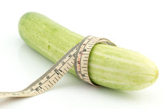 Long cucumber and measuring tape. Isolated on white Royalty Free Stock Photo