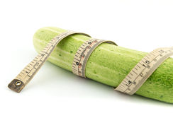 Long cucumber and measuring tape. Isolated on white Royalty Free Stock Image