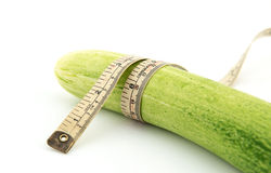 Long cucumber and measuring tape. Isolated on white Royalty Free Stock Photography