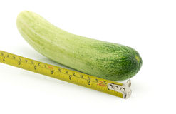 Long cucumber and measuring tape. Isolated on white Stock Image