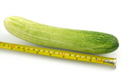 Long cucumber and measuring tape. Isolated on white Stock Photo