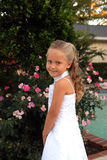 Long Curls. A pretty little girl dressed in a long white dress.  She has blonde Stock Photo