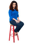 Long curly haired lady seated on red stool Stock Photos