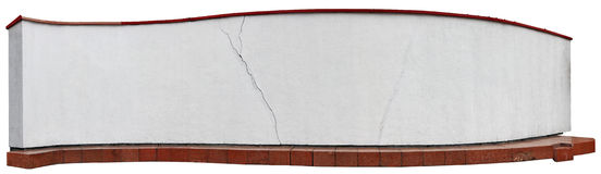 Long curve white wall with the basis from red granite blocks. Royalty Free Stock Images