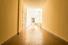 Long dark corridor with bright light from windows, light at the end of corridor. Abstract background Royalty Free Stock Image