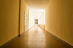 Long dark corridor with bright light from windows, light at the end of corridor. Abstract background Royalty Free Stock Photography