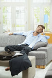 Long day. Tired businessman resting on couch at home after long day of work stock image